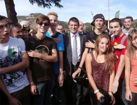 Kuvassa joukko ranskalaisnuoria sisäministeri Manuel Vallsin kanssa tekemässä quenellea.