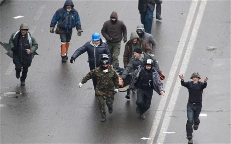 Mielenosoittajat kantavat ammuskelussa haavoittunutta miestä.