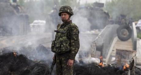 Ukrainalaissotilas vallatulla separatistien tiesululla Slovjanskissa . (Reuters)