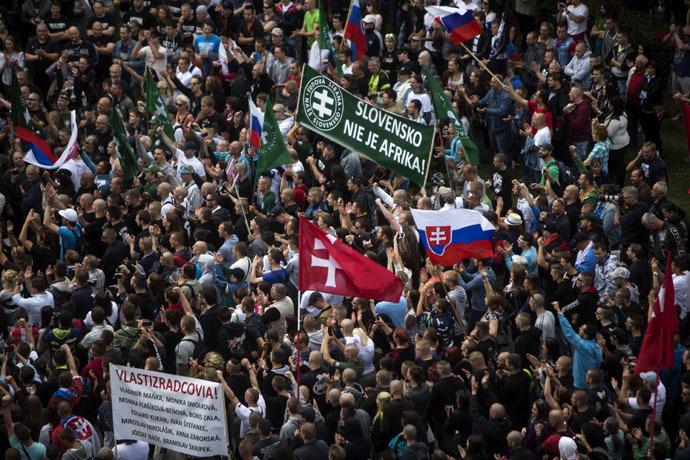 """Keskellä näkyvä kyltti julistaa osuvaa sanomaa: """"Slovakia ei ole Afrikka."""""""