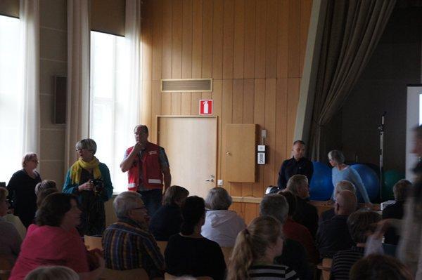 Kari Petäjä SPR:n liivissä, Juho Suoramaa ja Jaana Karrimaa juttelevat keskenään lavan reunalla.