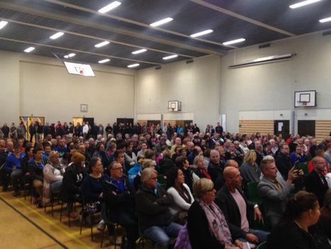 Länsi-Porin koulun sali täynnä ihmisiä, jotka eivät usko päättäjien vakuutteluja vastaanottokeskuksesta.