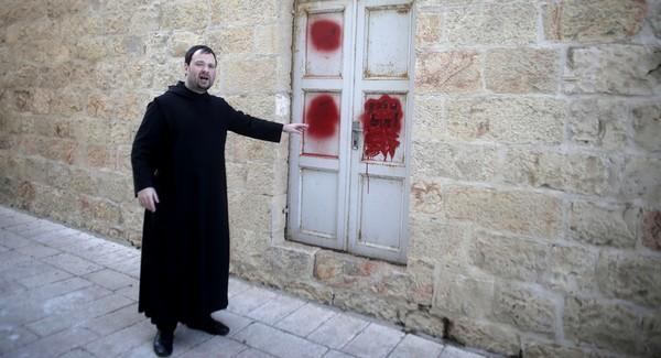 Isä Nikodemus osoittaa graffitia luostarin ovessa.