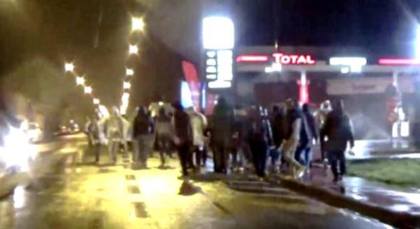 Paikalliset asukkaat kuvasivat kännyköillään laittomien siirtolaisten marssia pitkin Calais'n katuja.