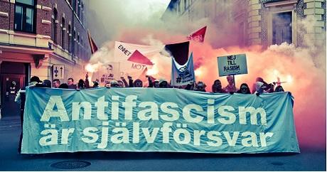 """Antifasismi on banderollin mukaan muka """"itsepuolustusta"""". Itsepuolustusta ruokaa jakaneen nationalistin kimppuun hyökänneiden henkilöidenkin väitetään käyttäneen."""